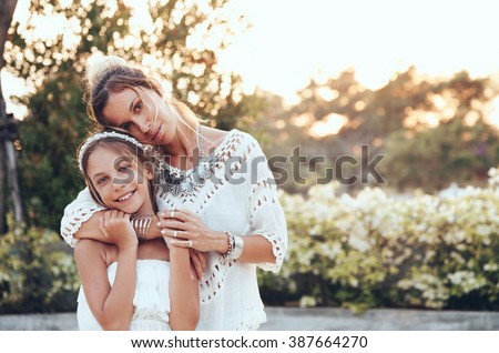 Tween daughter hugging with her mom in summer sunlight - stock photo