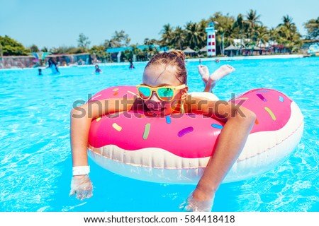 stock photo tween girl relaxing on the inflatable ring in water in the aqua park in thailand 584418418