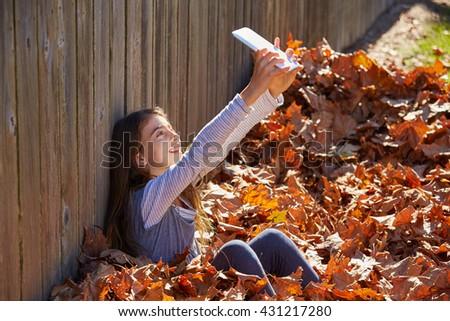 Tween kid girl selfie tablet pc in autumn leaves park - stock photo