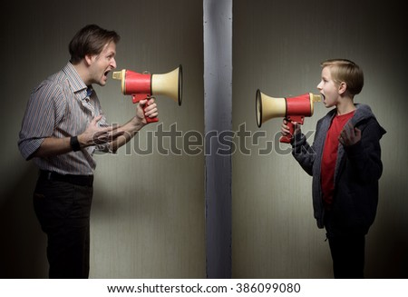 Tween son and his father yelling through the megaphones standing on either side of a wall - stock photo