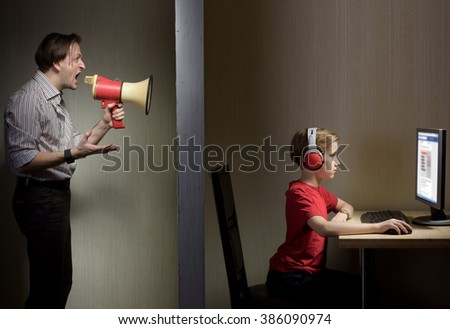 Tween son in headphones looks at a computer screen while his father yells at him through a megaphone - stock photo