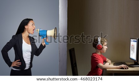 Tween son in headphones looks at a computer screen while his mother shouts at him through a megaphone