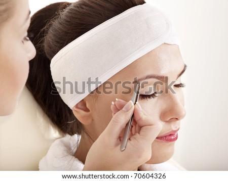 Tweezing eyebrow by beautician. Isolated. - stock photo