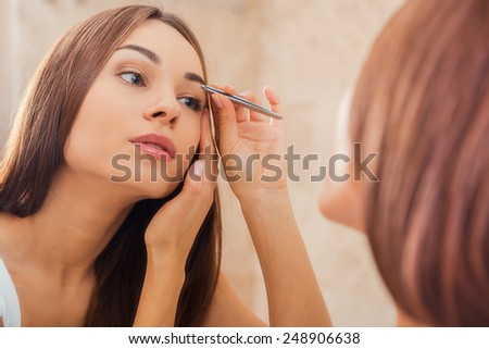 Tweezing eyebrows. Beautiful young woman tweezing her eyebrows while looking at the mirror - stock photo