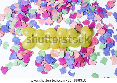 Twelve grapes and confetti for New Year's holiday - stock photo