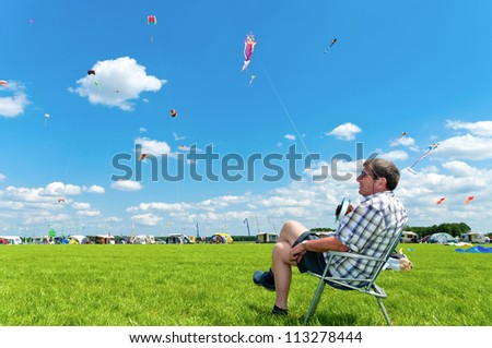 TWENTERAND, NETHERLANDS - JUNE 30: Man holds his kite at the 3rd international kite festival on june 30, 2012 in Twenterand, Netherlands.Most of the participants are from Germany & Belgium - stock photo