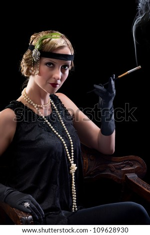 Twenties lady smoking a cigarette with a cigarette holder - stock photo