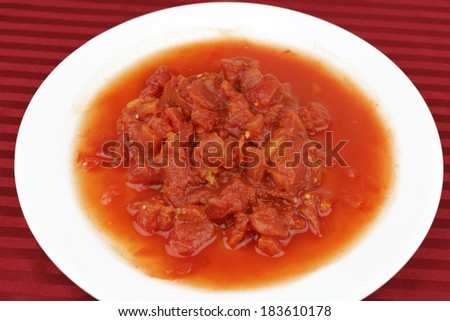 Twenty eight ounces of peeled and chopped red tomatoes with natural juice on a round white plate over a red striped table cloth background. - stock photo