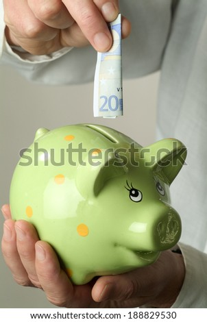 Twenty euro are plugged into a piggy bank. - stock photo