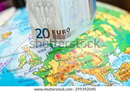 Twenty Euro banknote is worth on the globe next to Europe - stock photo