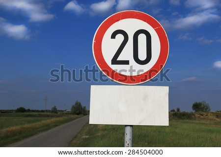 Twenty miles per hour speed limit sign against a partly cloudy sky - stock photo