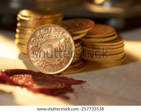 Twenty Swiss Francs gold coins Antique parchment paper sheets  - stock photo