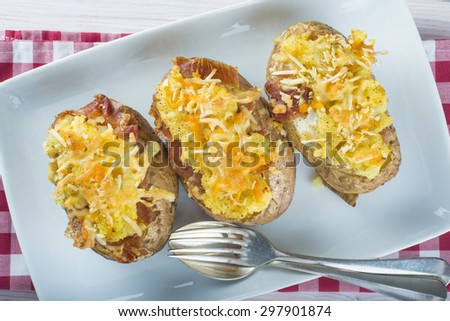 Twice baked potatoes stuffed with meat, jam, cheese and egg - stock photo