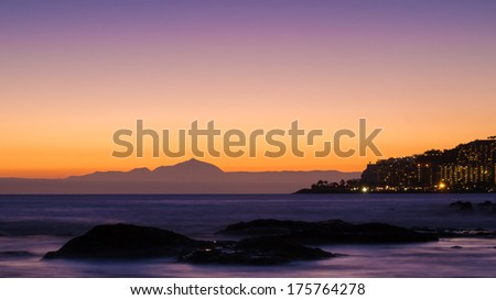 Twilight at the West Coast of Gran Canaria and the silhouette of Tenerife Island - stock photo