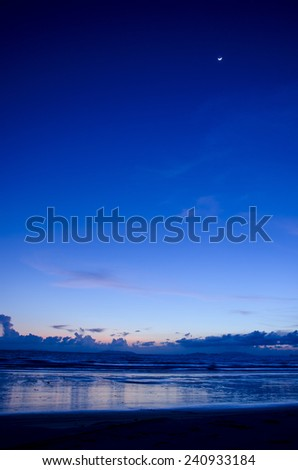 Twilight beach scene with moon on sky - stock photo