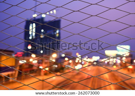 Twilight city behind the cage - stock photo