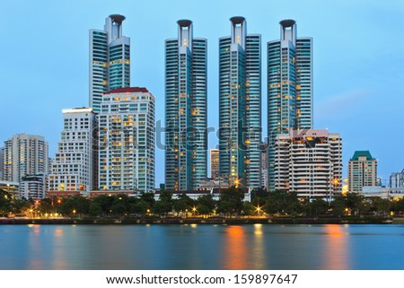 Twilight cityscape, office buildings and apartments in Thailand at dusk. View from public park.
