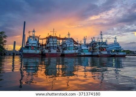 Twilight fishing boat of harbor in bay at Samut Songkhram Thailand. - stock photo