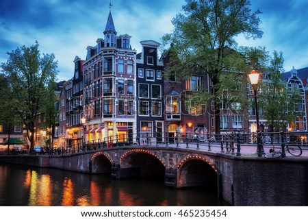 Twilight in city of Amsterdam, traditional Dutch houses and bridge over canal, corner of Grimburgwal and Oudezijds Voorburgwal, North Holland, The Netherlands