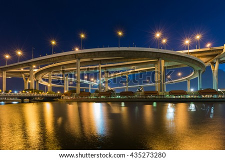 Twilight over Highway interchanged river front with reflection at night - stock photo