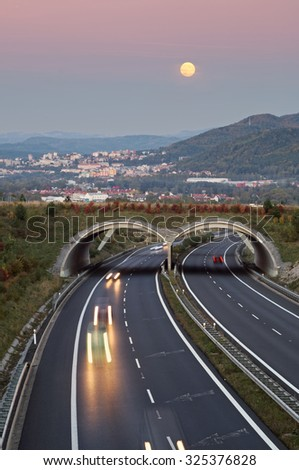 Twilight over the asphalt highway with ecoduct in the landscape. The rising full moon on rosy sky over the city in the distance. View from above. Town of Carlsbad in the Czech Republic - stock photo