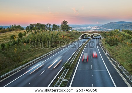 Twilight over the highway with ecoduct. The rising full moon on rosy sky over the city in the distance. Light path headlights cars traveling. Forested mountains in the background. View from above. - stock photo