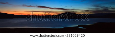 twilight panorama over the calm soft focused and colored lake  - stock photo