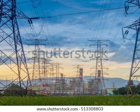 Twilight photo of High voltage post or High voltage tower in green field and power plant at Butterworth, Penang, Malaysia