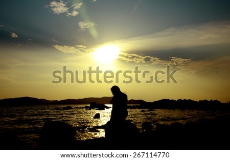 Twilight Scene. Sunset on the beach with a lonely girl - stock photo