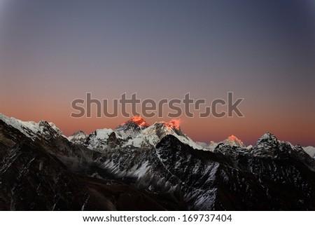 Twilight sky over Mount Everest, Nuptse, Lhotse and Makalu, in the Nepal Himalaya - stock photo