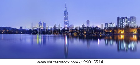Twilight skyline reflected in calm water, Nanjing, China - stock photo