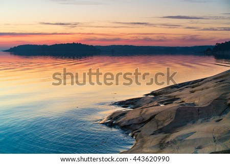 Twilight sunset view of the Scandinavian Baltic Sea and Swedish Archipelago with rocks in the foreground. Shot during mid summer festival
