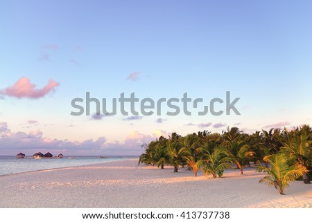 Twilight time at tropical beach with white sand, fresh turquoise sea and beautiful twilight sky in  Maldives. - stock photo