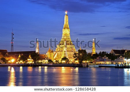 Twilight time of Wat Arun across Chao Phraya River during sunset in Bangkok, Thailand - stock photo
