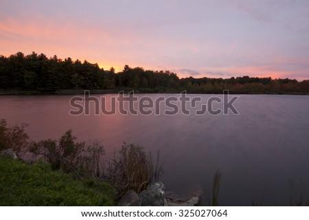 Twilight view of Pontoosuc Lake in Pittsfield, Massachusetts. - stock photo