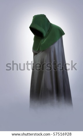 Twillight fog. Man in an medieval hood and cloak in the fog - stock photo