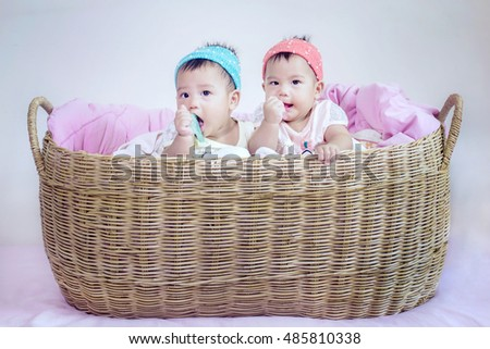 Twin asia baby in a basket.