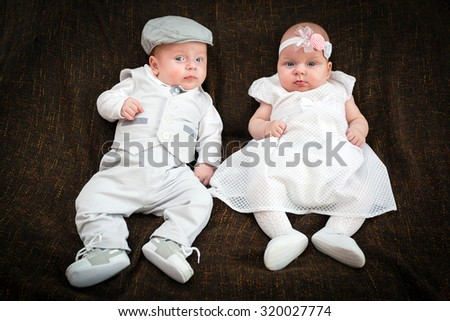 Twin babies dressed up for christening day - stock photo