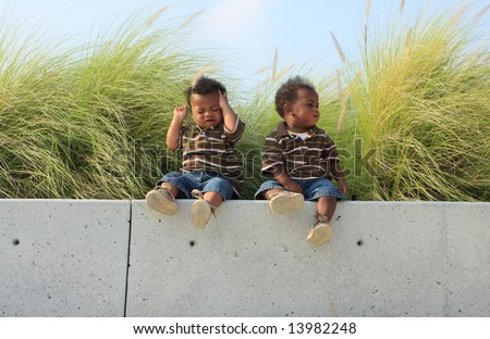 Twin Babies Sitting on a Ledge. - stock photo