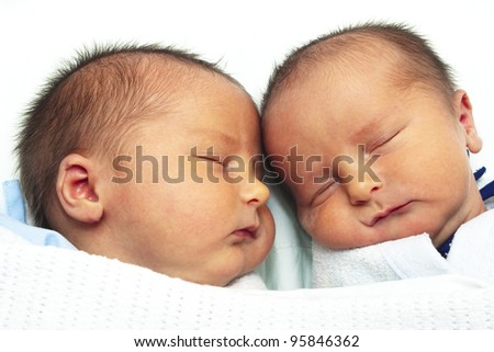 Twin baby boys lying close together - stock photo