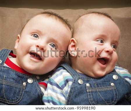 Twin boys in overalls smiling - stock photo
