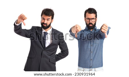 Twin brothers doing bad signal over white background