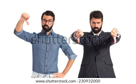 Twin brothers doing bad signal over white background - stock photo