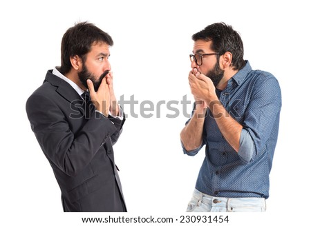 Twin brothers doing surprise gesture over white background - stock photo