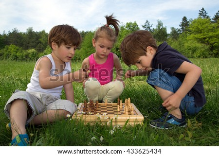 Twin Brothers Playing Chess In The Park While Cute Little Girl Watching The Game