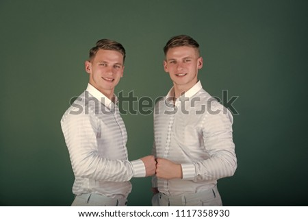 Twins fist each other
