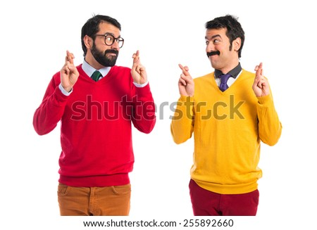Twin brothers with fingers crossing   - stock photo