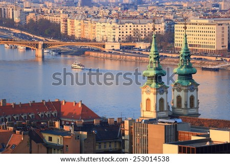 Twin church towers and distant Margaret bridge across Danube river, Budapest, Hungary - stock photo