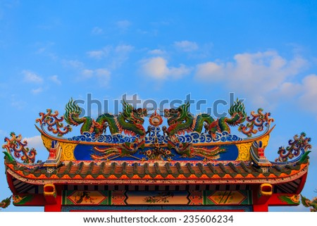 Twin dragons statue on the roof of Chinese temple with blue sky - stock photo