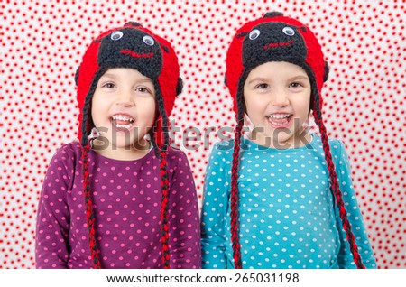 Twin girls are smiling at the camera and being happy. Little children are joyful. Child is wearing a woolen cap in the shape of ladybird on a background with red dots. Happy Children - stock photo